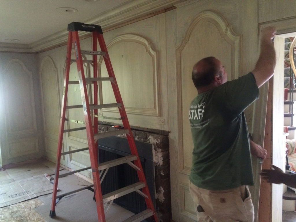 Deconstruction crew member removing door casing trim from a residential property.