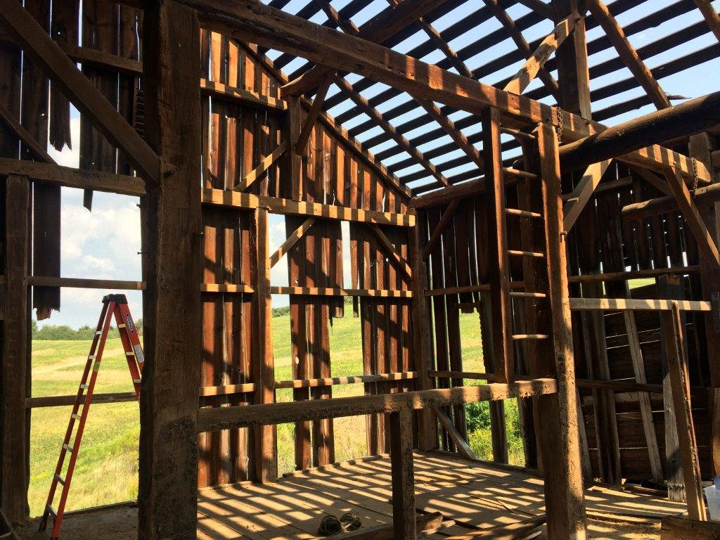 Interior of a barn deconstruction project. You can see the open framing and joists still standing with a step ladder in the background.