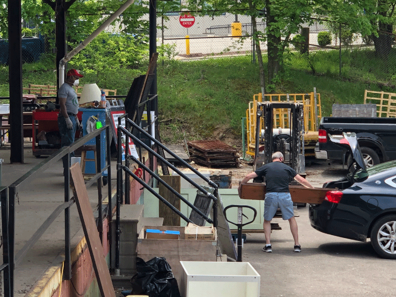 A donor unloads items from his car at our jetty COVID social distancing donation area.